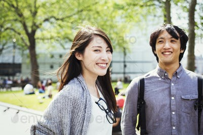Young Japanese man and woman enjoying a day out in London, standing in a park, smiling.