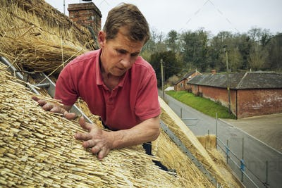 Man thatching a roof, layering the straw.