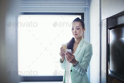 A business woman preparing for work, holding a cup of coffee and checking her smart phone.