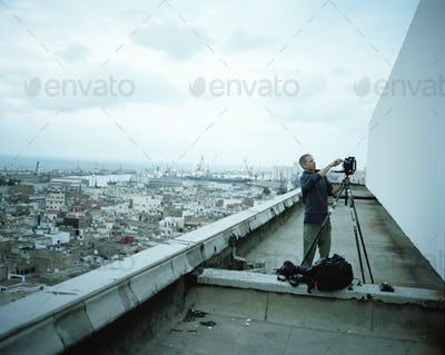Photographer standing on a rooftop in a city, setting up his camera on a tripod.