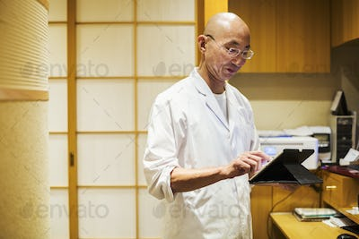 A chef in a small commercial kitchen, an itamae or master chef using a digital tablet.