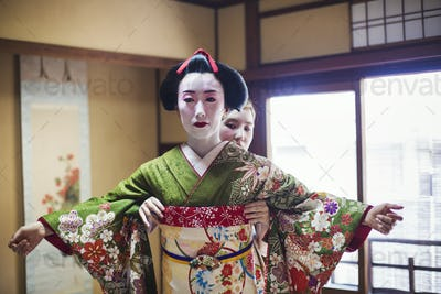 A geisha being dressed in the traditional kimono