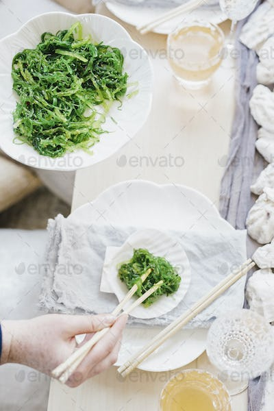 Overhead view of a table and a woman using chopsticks to eat vegetables.