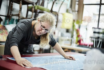 A woman measuring and marking the fabric for an upholstery task in a workshop.