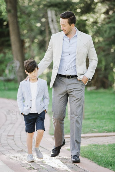 Father and son walking along a path in a garden.