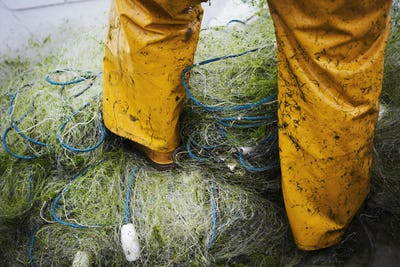 A fisherman in waders, standing on heaps of fishing nets.