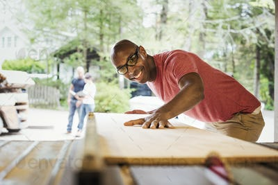 Man wearing glasses working in a lumber yard.
