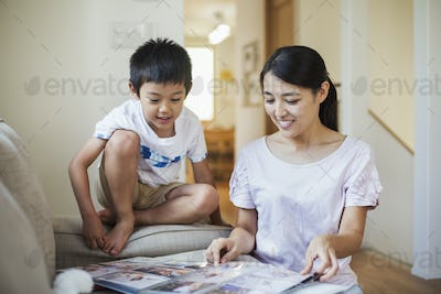 Family home. A woman and her son looking at a photographic album.