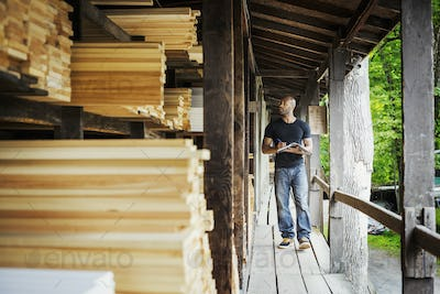 Man standing in a lumber yard, holding a folder, writing notes.