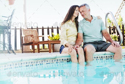 A couple seated side by side on the edge of a swimming pool.