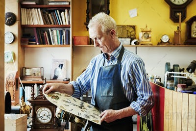 A clock maker holding an antique clock face looking at it.