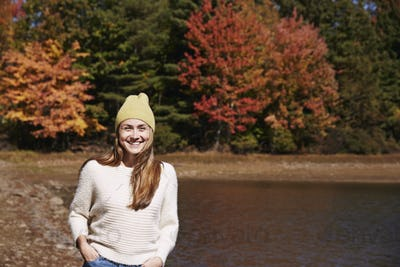A woman in jumper and woolly hat on the lake shore in autumn.