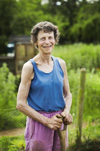A woman holding a shovel on a farm.