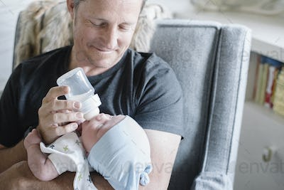 A father cradling a small baby and bottle feeding him.
