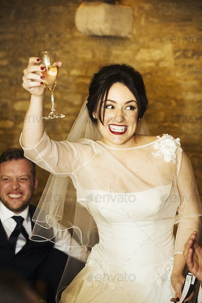 A bride on her wedding day raising her glass in a toast at the wedding party.