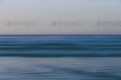 Ocean waves and the view to the horizon over the sea at dusk from the beach.