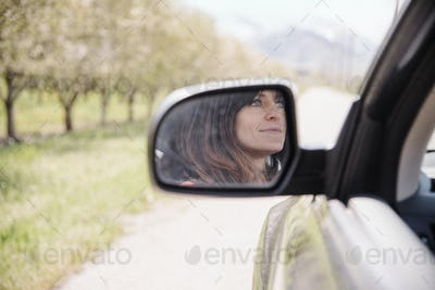 Woman in a car on a road trip, reflection seen in the side mirror.