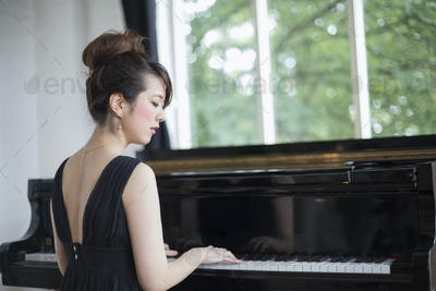 Young woman playing on a grand piano in a rehearsal studio.