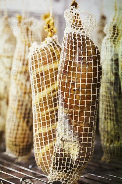 Close up of air dried meat wrapped in nets, hanging in a charcuterie.