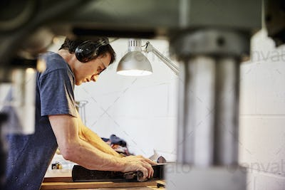 Man using a lathe to smooth wood