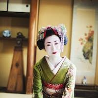 Geisha kneeling on floor