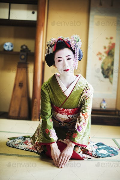 Geisha kneeling on floor