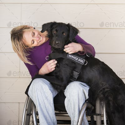A wheelchair user with her service assistance dog, a black labrador whose front paws are on her lap.