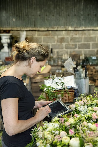 A woman florist using a digital tablet in a workshop.