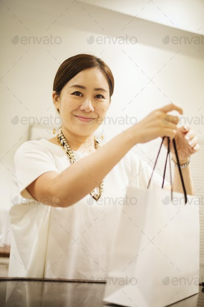 Woman working in a fashion boutique in Tokyo, Japan, holding shopping bag.