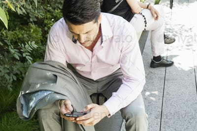 Businessman wearing a grey suit and pink shirt sitting outdoors, using his cell phone.
