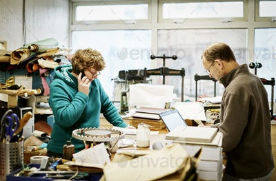A woman taking a phone call and a man workng on a laptop computer in a bookbinding workshop.