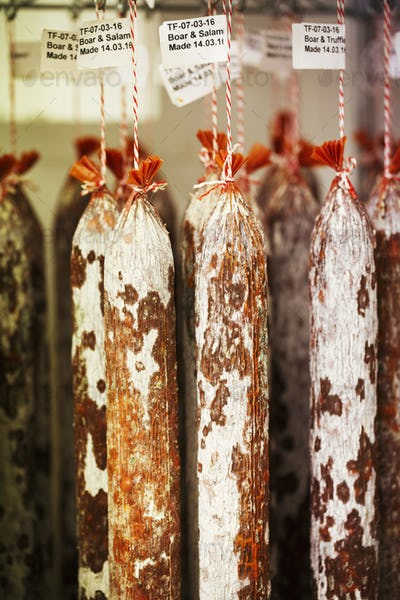 Close up of Chorizo sausages hanging from hooks in a charcuterie.