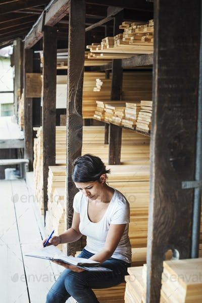 Woman sitting in a lumber yard, holding a folder.