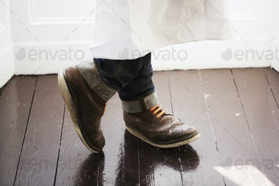 Close up of a man's feet, wearing brown shoes with orange shoe laces.