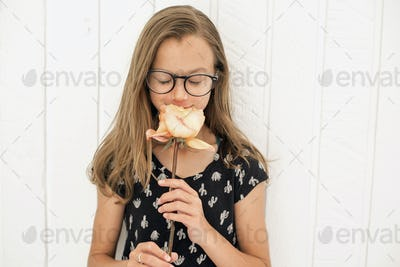Girl with spectacles smelling a rose.