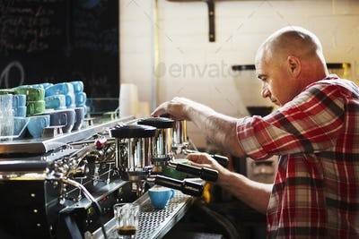 Specialist coffee shop. A man working a coffee machine making coffee.