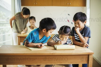 A group of children in a classroom with their female teacher.