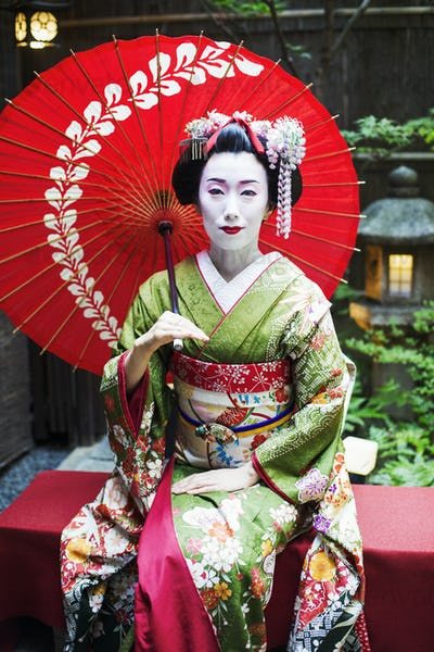 A traeditional geisha wearing a kimono and obi, seated holding an umbrella.