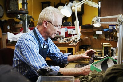 A clock repairer, a craftsman in his workshop using a laptop.