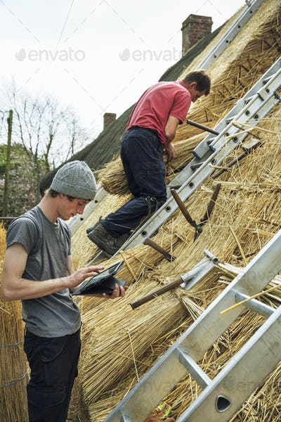 Two thatchers thatching a roof, one using a digital tablet the other standing on a ladder.