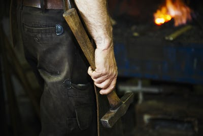A man in a leather apron holding a hammer in a workshop.
