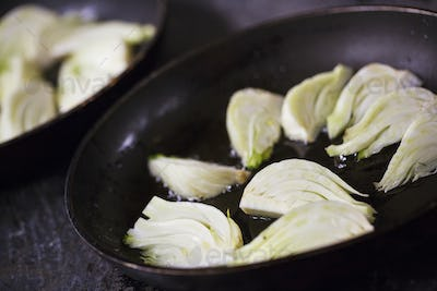 Close up of sliced fennel in a frying pan.