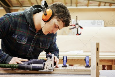 A young man using tools to shape a piece of wood in a  furniture workshop.