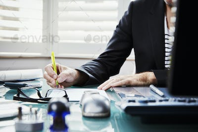 A man sitting at a desk in an office, holding a pen.