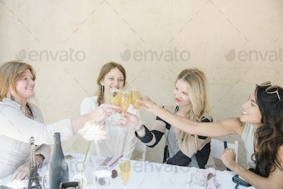 Four smiling women sitting at a table, holding glasses of champagne, toasting.