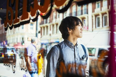 Young Japanese man enjoying a day out in London, walking past a shop window.
