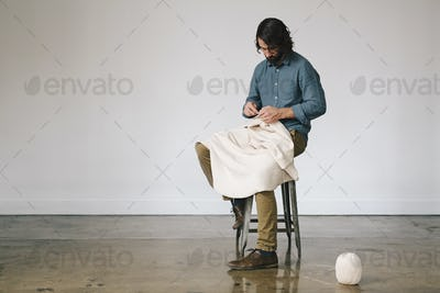 A male artist working, using string to crochet and create an art piece.
