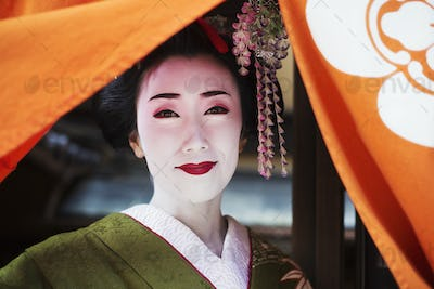 A traeditional geisha lifting an orange curtain.