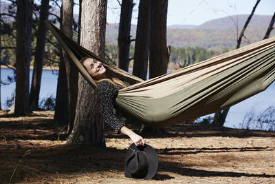 A woman lying in a hammock relaxing, under the pine trees by a lake.