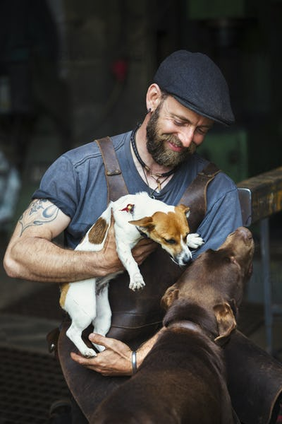 A man in a leather apron playing with two dogs in a workshop.
